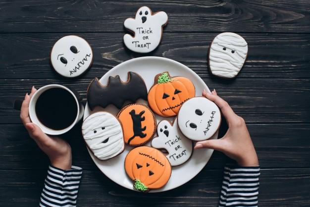 fille-se-prepare-pour-halloween-boire-du-cafe-manger-biscuits-effrayants_1429-1020